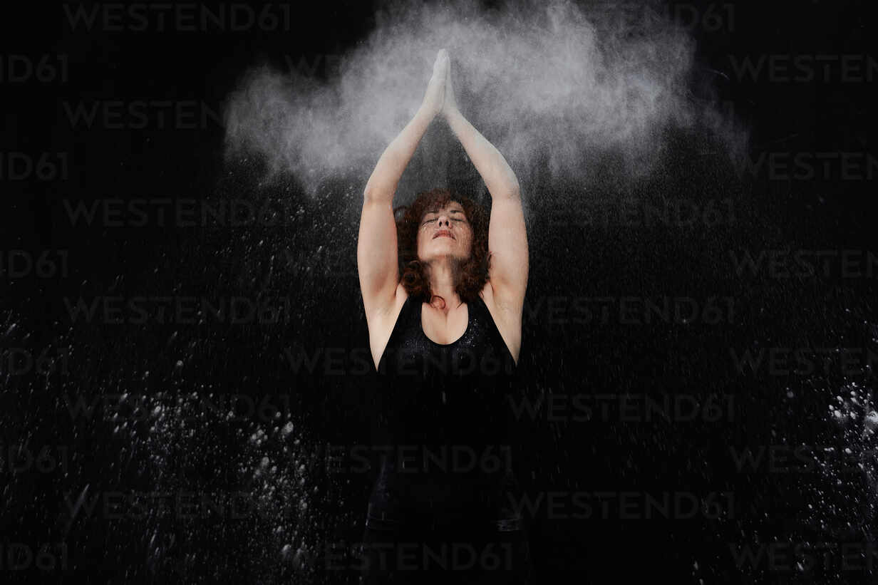 Woman clapping over head with white dust against black background - VEGF02801 - Veam/Westend61