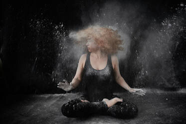 Woman tossing hair covered in white dust while sitting against black background - VEGF02807