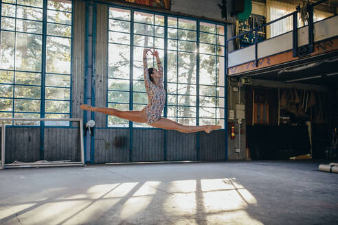 Side view of young slim ballerina in gymnastic suit jumping while practicing dance movements in light spacious studio with large window - ADSF11325