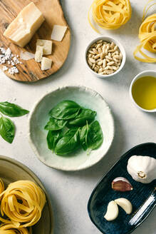 Basil leaves and ingredients for pesto sauce on plates on table - ADSF11396