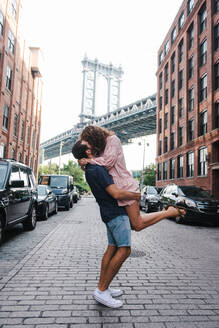 Side view of boyfriend lifting girlfriend while standing on street in New York - ADSF11453