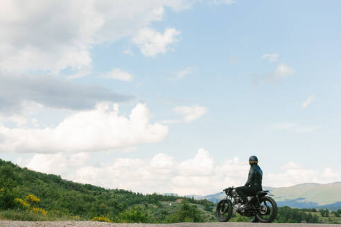 Young male motorcyclist on vintage motorcycle looking out over landscape, Florence, Tuscany, Italy - CUF56269