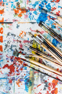 Still life of paintbrushes on colourful painted surface, overhead view - CUF56344