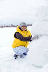 Woman making snowman, winter time, Moscow region, Russia - KNTF05223
