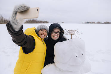 Smiling couple taking selfie with snowman - KNTF05226