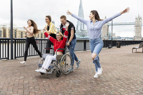 Carefree men and women with disabled female friend spending leisure time in city, London, UK - WPEF03292