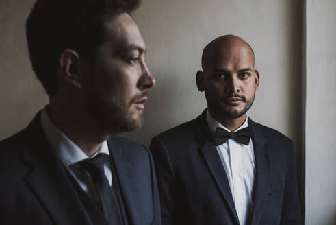 Gay couple in suits standing against wall on wedding day - DSIF00097