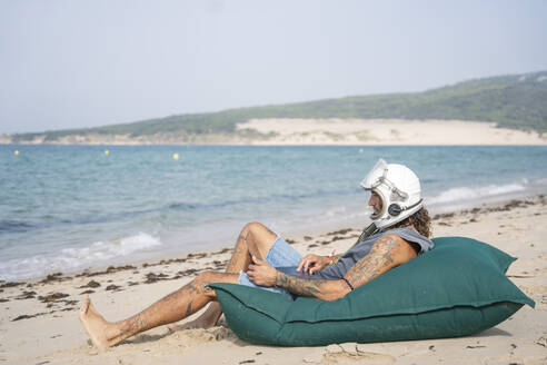 Man in space helmet using laptop while relaxing on large pillow at beach, Tarifa, Spain - OCMF01650