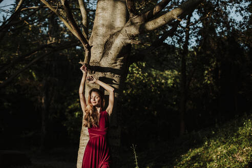 Beautiful woman standing against tree in forest on sunny day - GMLF00438
