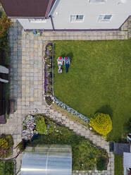 Aerial view of couple sitting in garden - KNTF05260