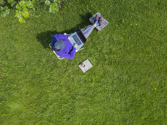 Woman using laptop in garden - KNTF05263