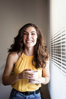 Cheerful young woman holding coffee cup while standing by window blinds at home - EBBF00596