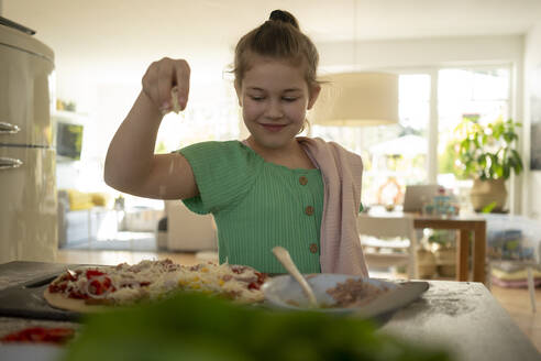 Cute girl preparing pizza with napkin over kitchen island - JOSEF01527