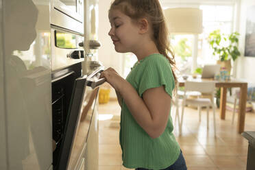 Smiling girl looking inside oven while standing in kitchen - JOSEF01533