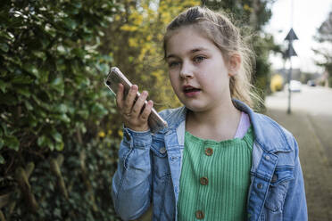 Girl with smart phone standing by trees in park - JOSEF01536