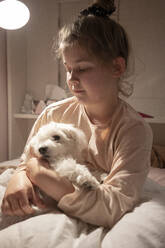 Cute girl holding dog while sitting in bedroom - JOSEF01551