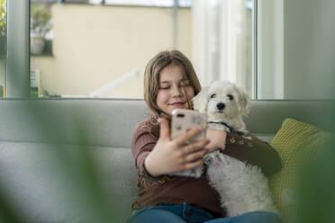 Girl taking selfie through smart phone with dog on sofa - JOSEF01563