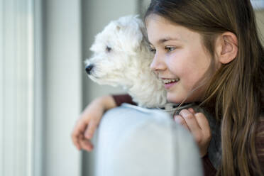 Cute smiling girl with dog looking away in living room - JOSEF01566