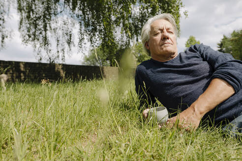 Contemplating man with cup lying on side over grass in backyard - GUSF04394