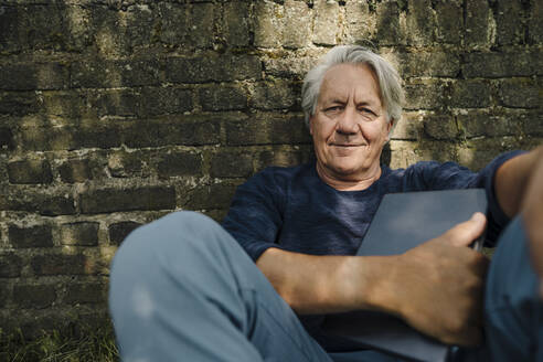 Smiling wrinkled man with laptop sitting against brick wall in yard - GUSF04397