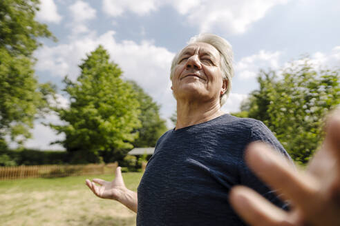 Confident wrinkled man with eyes closed enjoying in field during sunny day - GUSF04424
