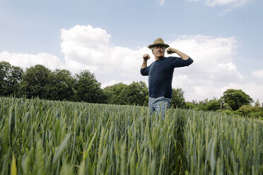 Confident man flexing muscles against cloudy sky in field - GUSF04430