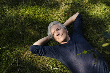 Confident smiling man lying down in field - GUSF04433