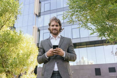 Beard young male professional with smart phone while standing against office building - VPIF02941