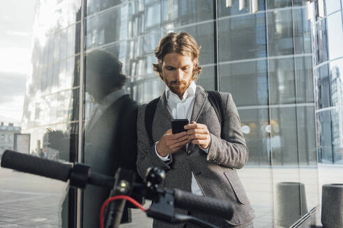 Professional using smart phone while leaning on glass by electric push scooter in financial district - VPIF02956