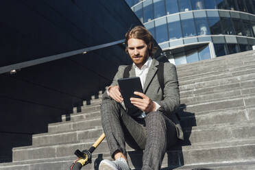 Young male entrepreneur using digital tablet while sitting with electric push scooter on steps in financial district - VPIF02968