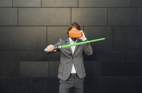 Young businessman playing video game through virtual reality simulator while holding sword against wall at downtown - VPIF02974