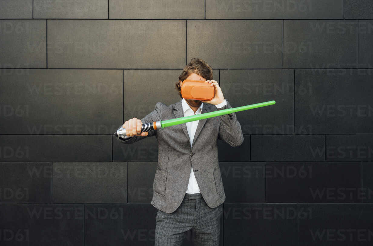 Young businessman playing video game through virtual reality simulator while holding sword against wall at downtown - VPIF02974 - Vasily Pindyurin/Westend61