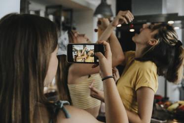 Teenage girl filming friendswith her smartphone, eating cherries - MFF06056