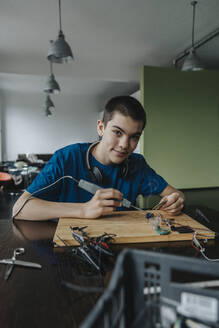 Boy sitting at home using soldering iron - MFF06059