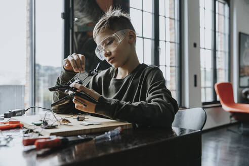 Boy assembling miniature helicopter at home - MFF06065
