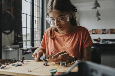 teenage girl tinkering with soldering iron at home - MFF06068
