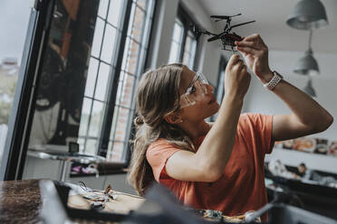 Teenage girl assembling miniature helicopter at home - MFF06071
