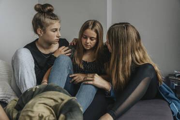 Girlfriends consoling sad teenage girl - MFF06080