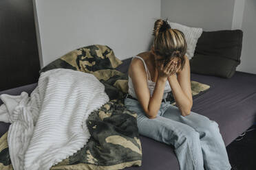 Despaired teenage girl sitting on bed, covering face with hands - MFF06083