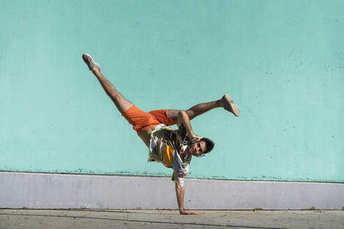 Casual man doing handspring in front of green wall - AFVF06994