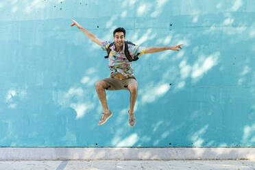 Casual man jumping in front of blue wall - AFVF07003