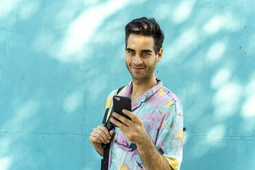 Attractive man standing in front of blue wall, using smartphone - AFVF07006