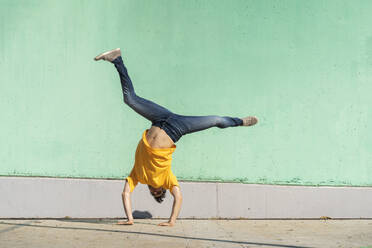 Casual man doing handspring in front of green wall - AFVF07009