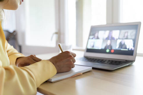 Cropped hands of female entrepreneur writing on diary while talking with colleagues through video conference at home - AFVF07054