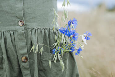 Bouquet of blue flowers and oat in the pocket of green dress - EYAF01261