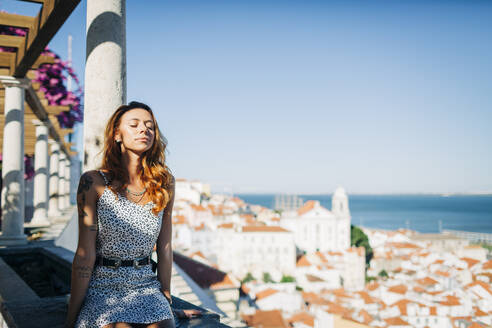 Woman resting while sitting on retaining wall at Alfama, Lisbon, Portugal  - DCRF00651