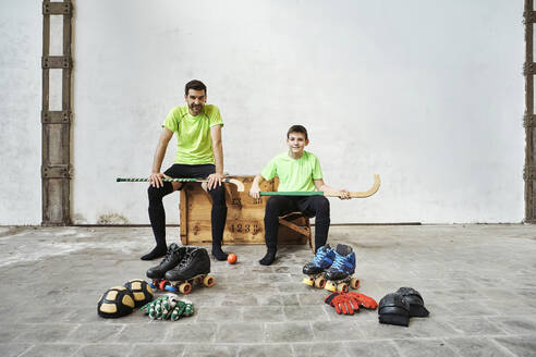 Father and son sitting with hockey sticks on wooden box by sports equipment against wall at court - VEGF02813