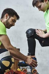 Man helping son wearing roller skate before training - VEGF02819