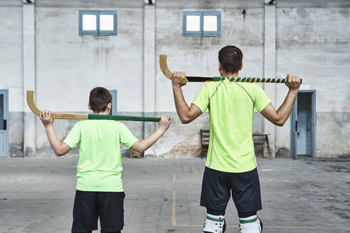 Father and son in uniform holding hockey sticks at sports court - VEGF02825