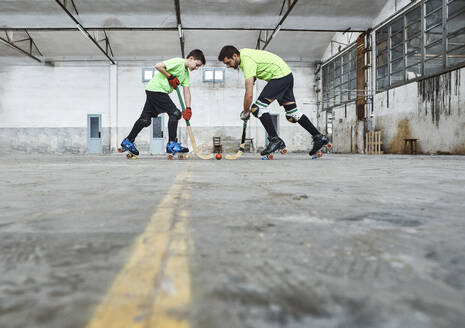 Surface level view of father and son in face off while playing roller hockey on court - VEGF02828